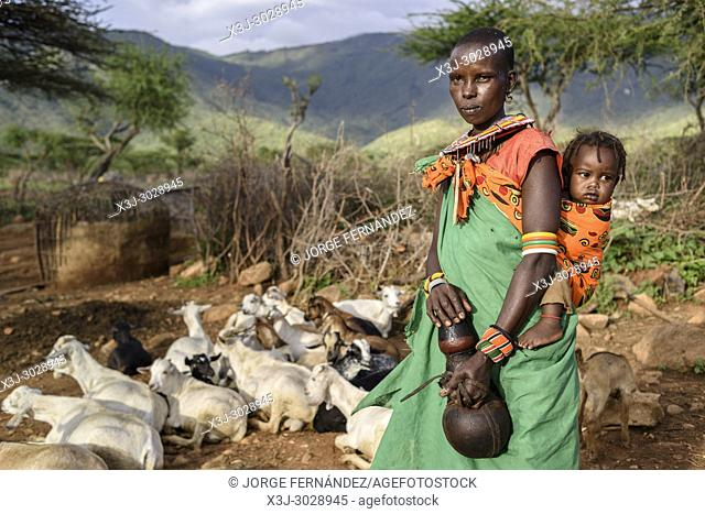African woman with her baby milking goats inside a small cluster of huts