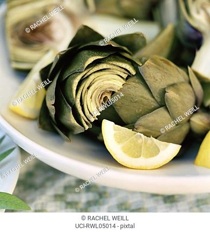 Close up of artichoke hearts with lemon wedges