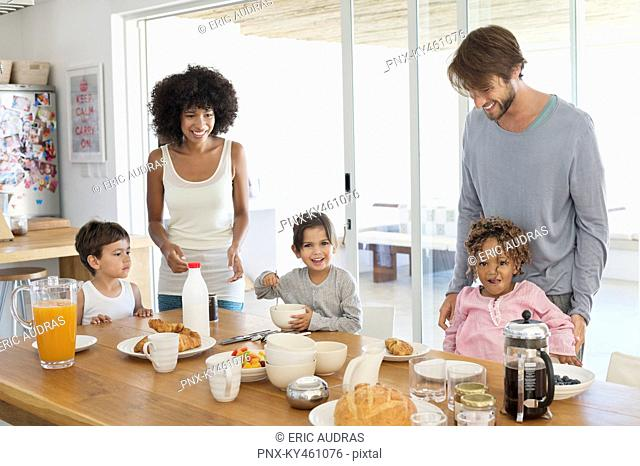 Family smiling at a breakfast table
