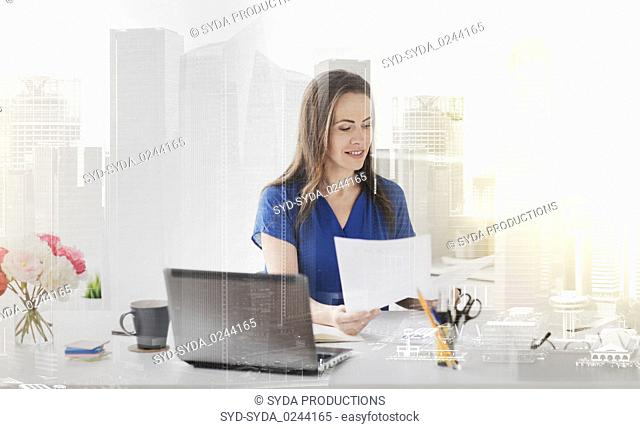 happy woman with papers and laptop at office
