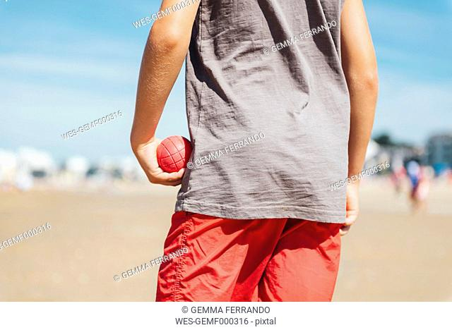 Back view of boy standing on the beach holding red boccia bowl in his hand