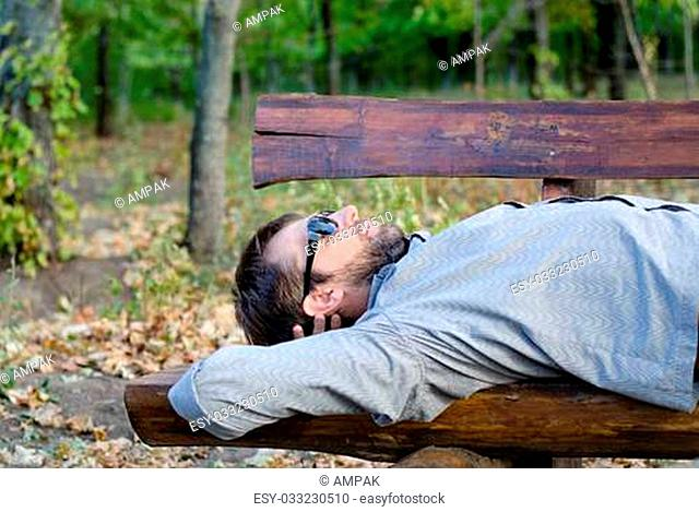 Man sleeping on a rustic wooden bench lying back on the seat in the sunshine with his sunglasses on