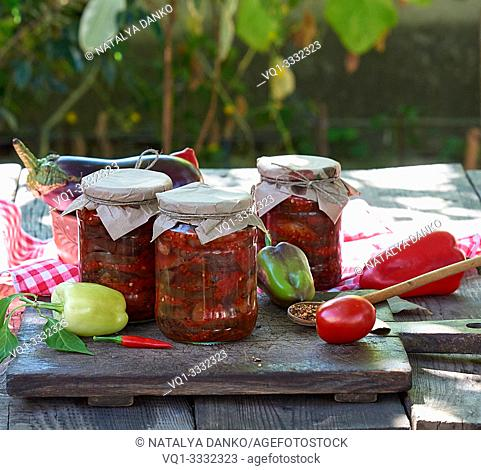Canned eggplant slices in spicy vegetable sauce in glass jars on a wooden table