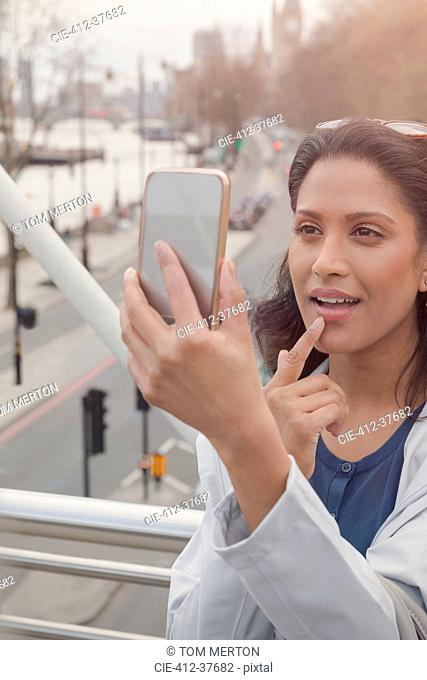 Woman checking makeup with camera phone on urban bridge, London, UK