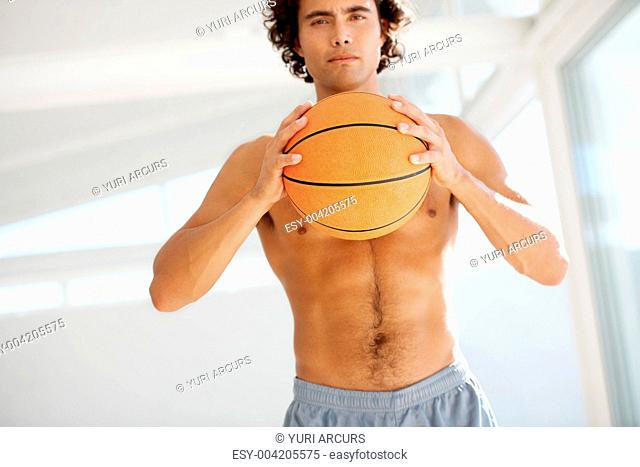 Gorgeous young man wearing no shirt holding a basketball