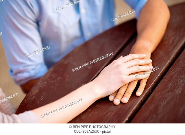 Cropped view of couple holding hands at table