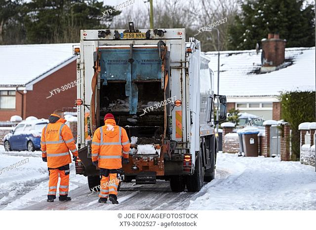 workers with refuse recycling collection truck driving along street covered in snow in newtownabbey northern ireland