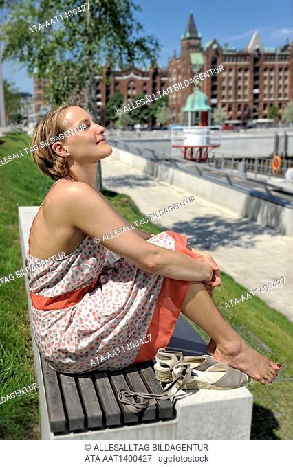 Woman sitting on a bench enjoying the sun