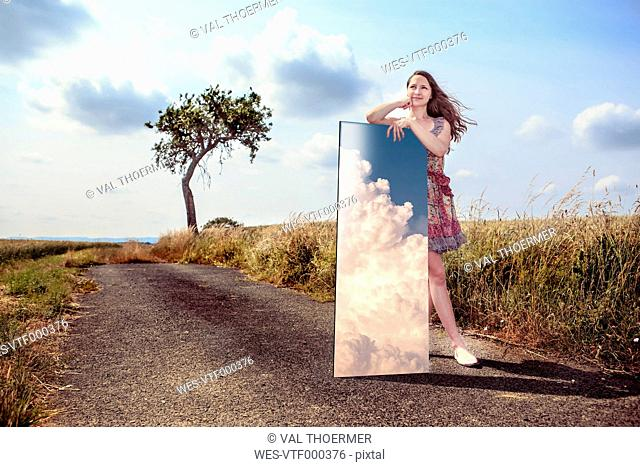 Teenage girl with mirror in rural landscape