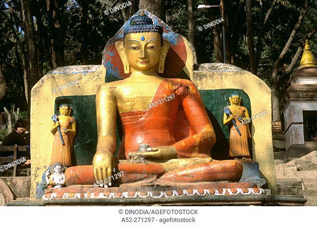 Seated Buddha statue on Eastern stairway at base of hill to Swayambhunath Temple. Katmandu. Nepal