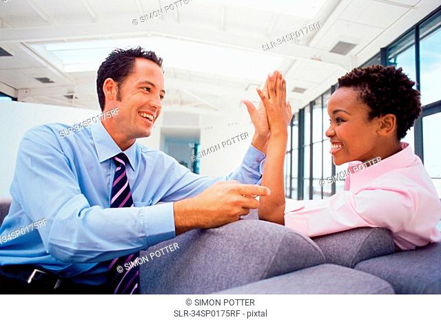 Business people high fiving on couch