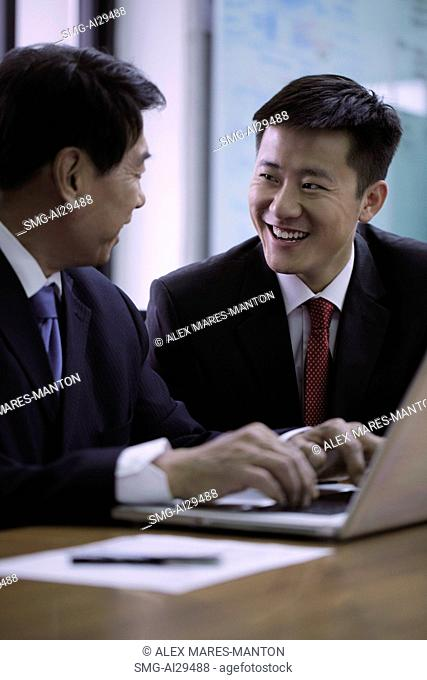 Businessmen smiling at each other while working on laptop