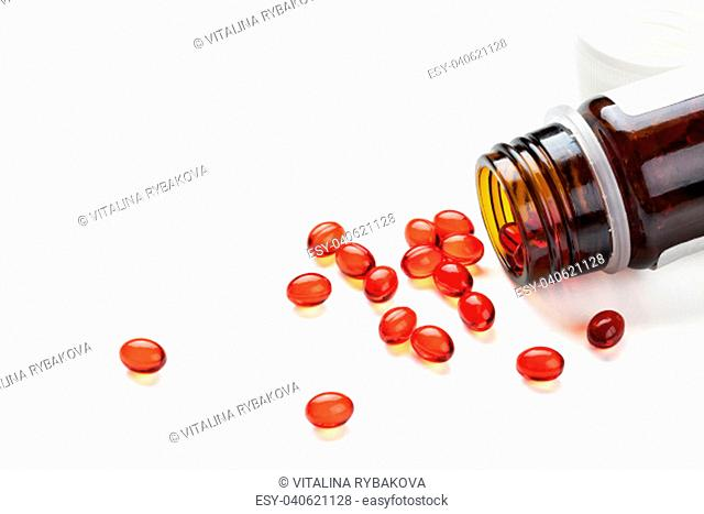 Closeup shot of red capsules. Isolated on white background