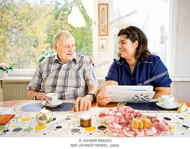 Nurse with senior man at table, Sweden