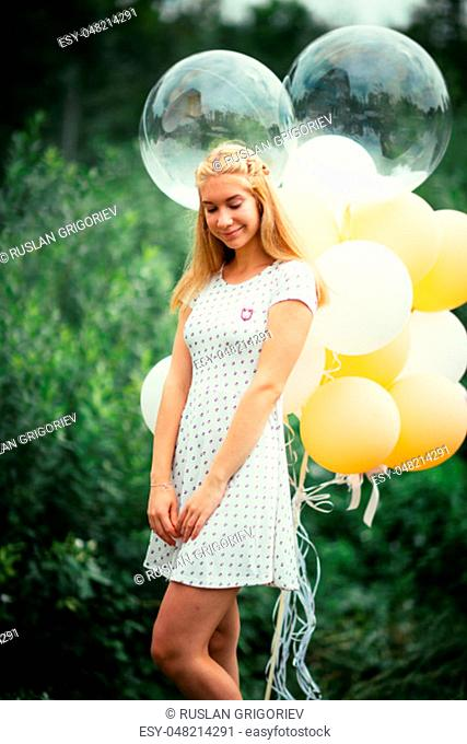 young girl with balloons on nature background