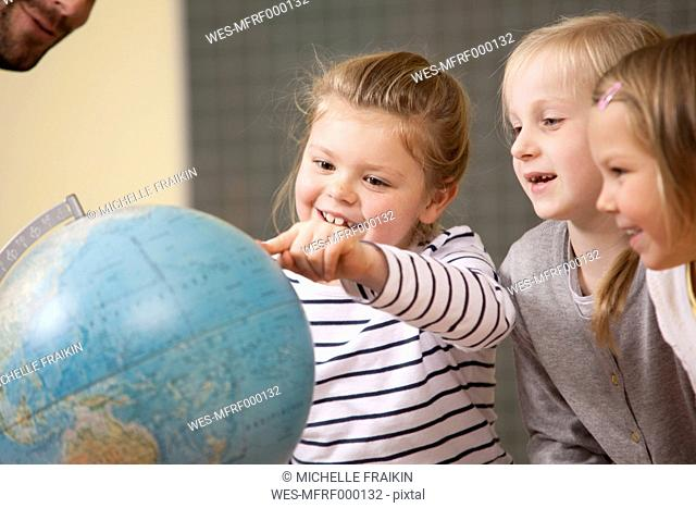 Smiling schoolgirls pointing at globe in classroom