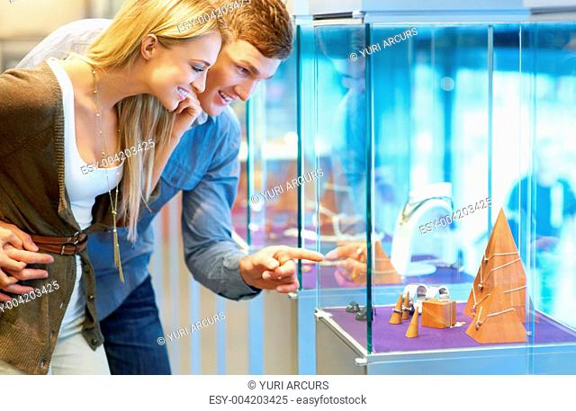 Attractive young couple looking at jewellery in a display cabinet