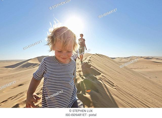 Mother and sons walking on sand dune, Dune 7, Namib-Naukluft National Park, Africa