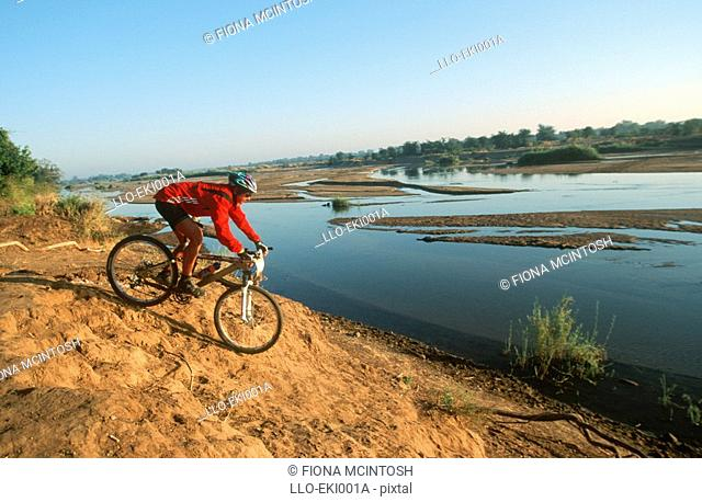 Mountain Biker Desending to the Riverbank  Kruger National Park, Limpopo Province, South Africa