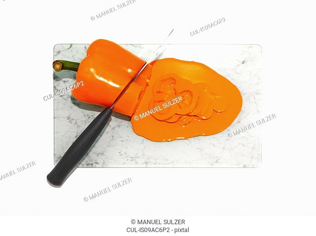 Kitchen knife cutting orange pepper