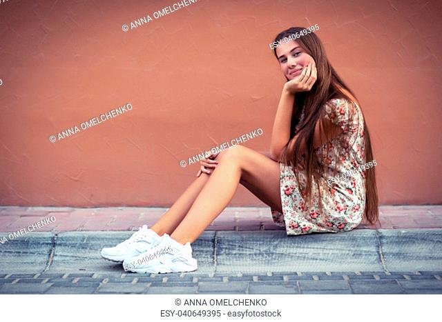 Pretty girl on the street, nice female with long natural hair sitting on blank monophonic wall background, authentic genuine beauty of young people