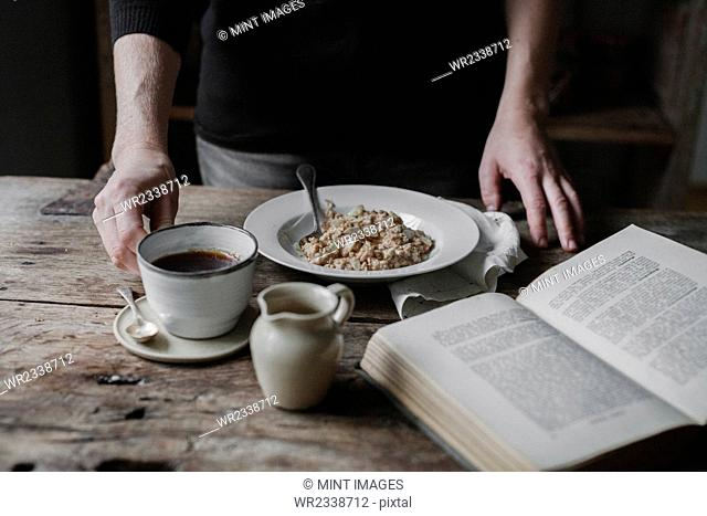 A person at a table with a cup of coffee, bowl of muesli and an open book