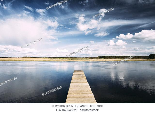 Gomel, Belarus. Old Wooden Boards Pier On Calm Water Of Lake Or River At Evening Or Morning Time. Forest On Other Side. Landscape. Nature Background