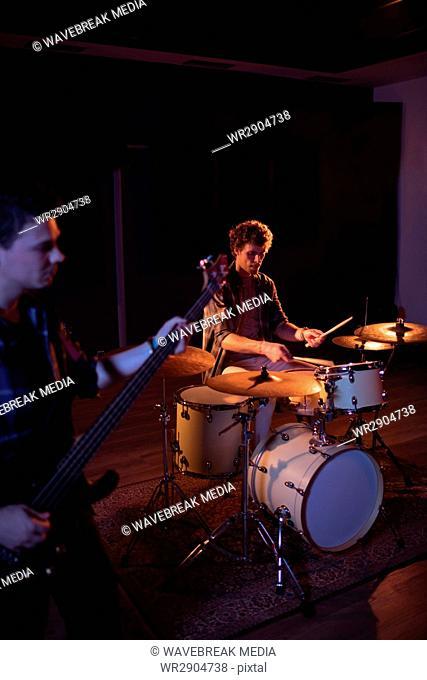 Drummer and guitarist practicing in recording studio