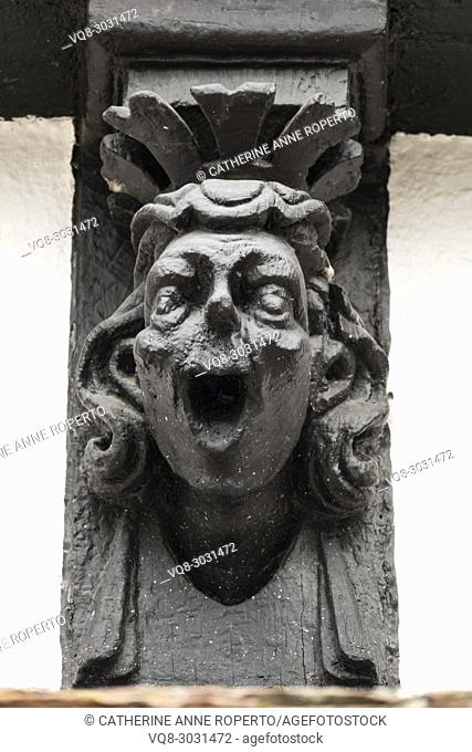 Comic black lacquered wooden finial of a laughing man with stylised crown on the old timber framed museum of Hereford, England