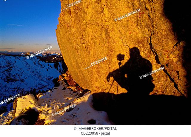 Shadow of a photographer short time after sunrise at the snowy mount Plankenstein, Risserkogel, Upper Bavaria, Alps, Germany