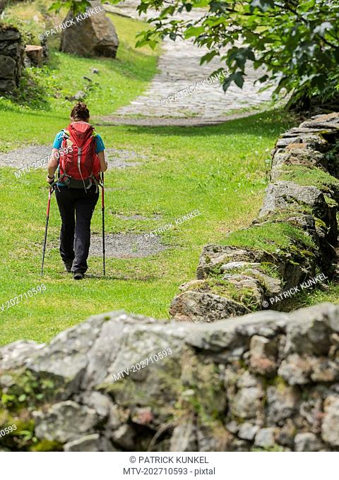 Woman hiking in the High Pyrenees on old road in village of Heas, France