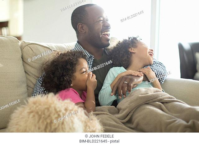 Father and daughters watching television on sofa