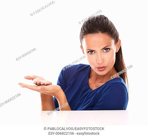 Charming woman in blue shirt holding palms up while looking at you in white background - copyspace