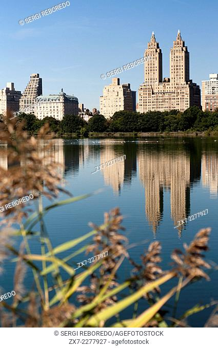 Skyline of Central Park West seen from the Lake in Central Park New York City. The Central Park Lake, in conjunction with the Ramble