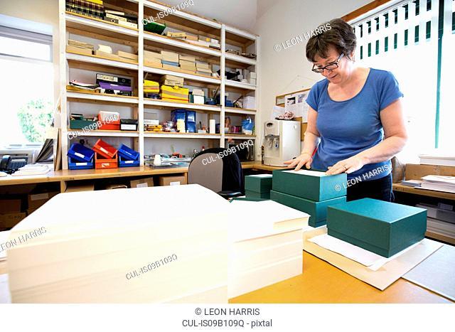 Female worker packing order in cardboard box in printing press workshop