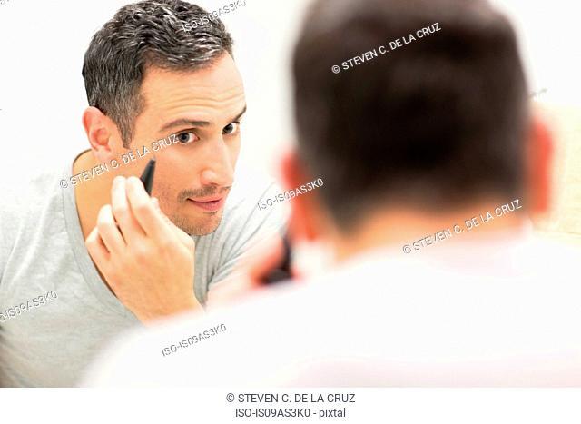 Mid adult man, looking in mirror, using tweezers, rear view