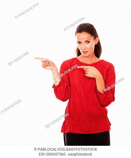 Portrait of pretty latin woman on red shirt pointing to her right while standing and looking at you on isolated background - copyspace