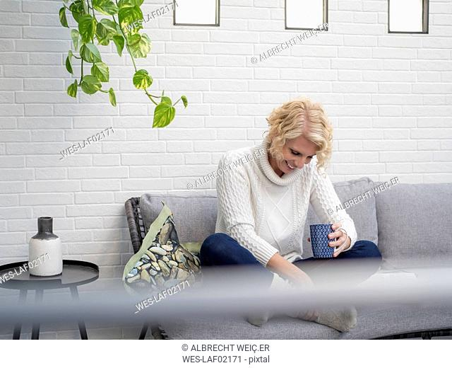 Smiling mature woman sitting on couch at home holding coffee mug