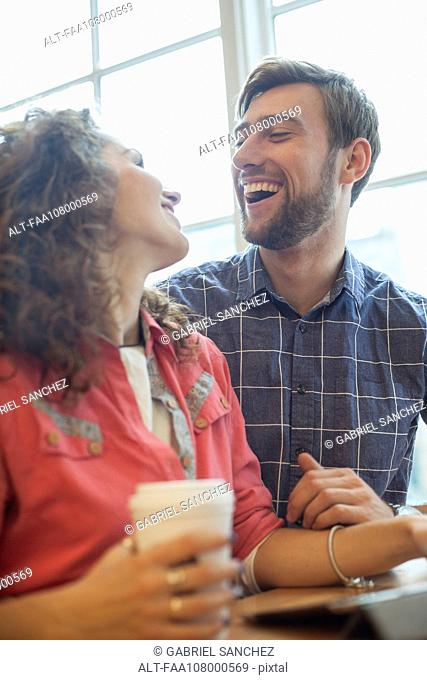 Couple laughing together in coffee shop