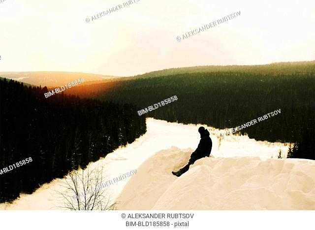Caucasian hiker sitting on snowy mountain