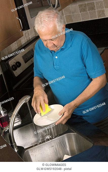 Close-up of a senior man cleaning a plate in the kitchen