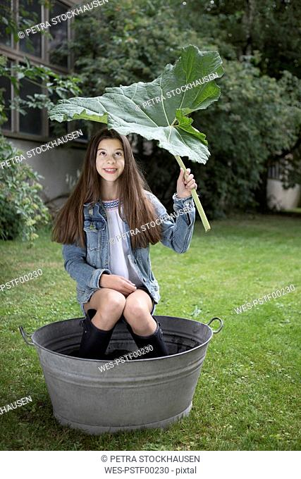 Portrait of smiling girl sitting under big in tub in in the garden