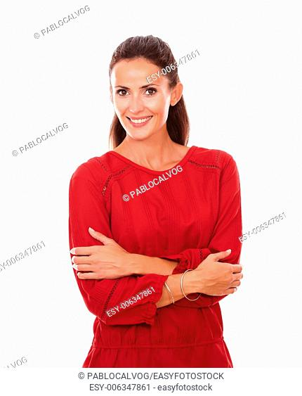 Portrait of cheerful adult lady on red shirt with crossed arms smiling at you on isolated white background