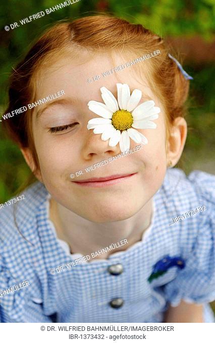 Girl with daisy flower on her face, flower power