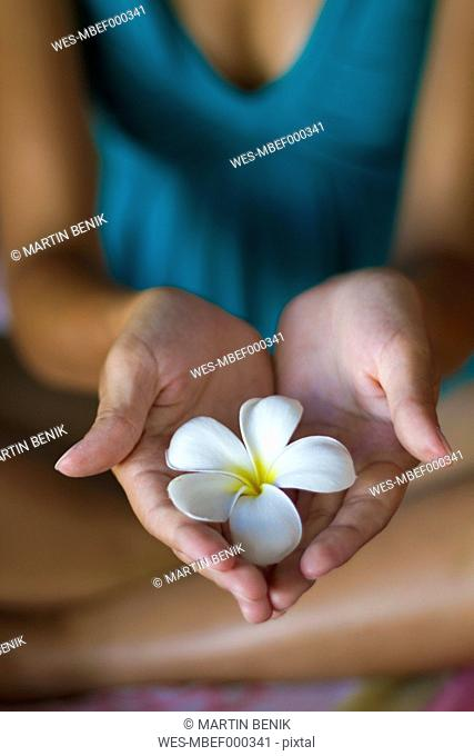 Indonesia, Young woman with spa flower