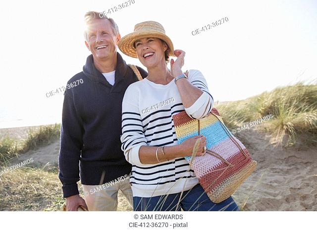 Smiling mature couple on sunny beach