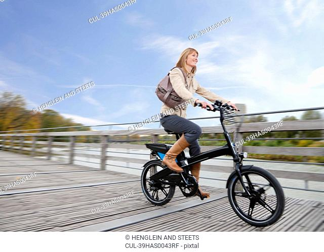 Woman riding bike on wooden walkway