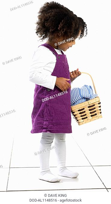 Young girl (3 years) holding basket of clothing