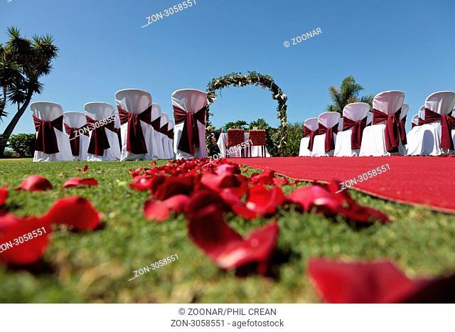 Outdoor wedding setting with red carpet flower petals white covered chairs and a romantic arch