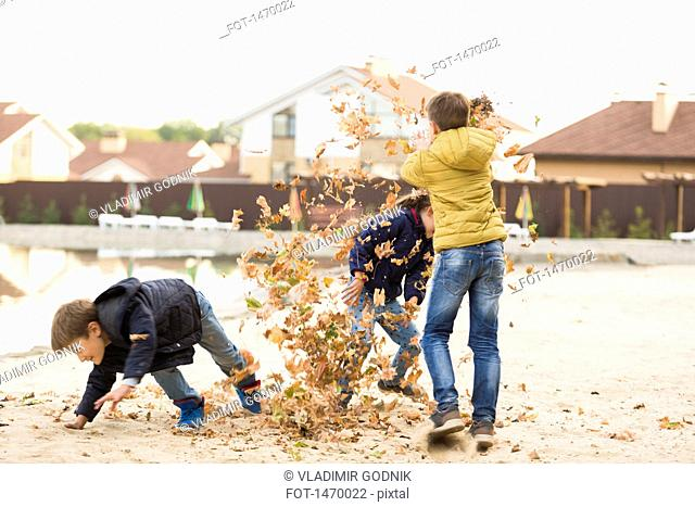 Children playing with dry leaves on footpath